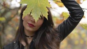 Één vrouw stellen het Van het Middenoosten met een droog blad in dalingsseizoen stock video