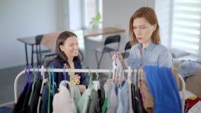 Één vrouw zet kleding op hanger in ruimte en haar vrouwelijke vriend is scherpe draden met grappig gezicht stock video