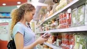 Één vrouwelijke persoon kiest producten in grote markt stock video