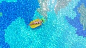 Één vrouwenrust in een blauwe pool, die op een matras drijven stock footage