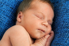 Één week oude baby op witte algemene en vrouwelijke hand Royalty-vrije Stock Afbeelding