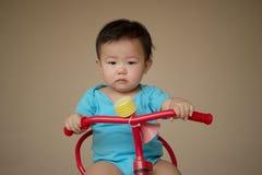 1 éénjarige Chinese Aziatische jongen die kruippakjes dragen die een fiets berijden Royalty-vrije Stock Fotografie