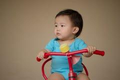 1 éénjarige Chinese Aziatische jongen die kruippakjes dragen die een fiets berijden Royalty-vrije Stock Afbeeldingen