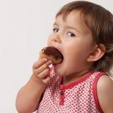 2 éénjarigenbaby die snoepjes met gulzigheid eten Stock Foto's