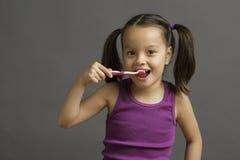 5 éénjarigenjong geitje die haar tanden borstelen stock foto