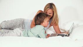 4 éénjarigenjongen die met zijn moeder in bed liggen en met notitieboekje spelen stock videobeelden