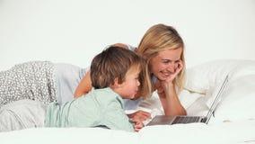 4 éénjarigenjongen die met zijn moeder in bed liggen en met notitieboekje spelen stock video