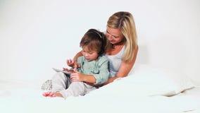 4 éénjarigenjongen die met zijn moeder in bed ligt en met tablet speelt stock video
