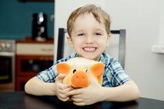 4 éénjarigenjongen die terwijl het houden van een spaarvarken glimlachen Stock Afbeelding