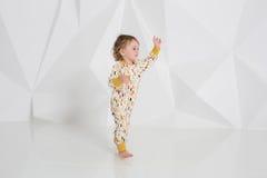 Éénjarigenkind die zich dichtbij witte muur in studio bevinden Royalty-vrije Stock Afbeeldingen