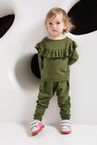 Éénjarigenkind die zich dichtbij witte muur in studio bevinden Royalty-vrije Stock Fotografie