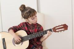 10 éénjarigenmeisje die de Spaanse gitaar spelen Stock Afbeelding