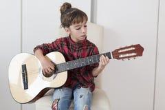 10 éénjarigenmeisje die de Spaanse gitaar spelen Royalty-vrije Stock Foto's
