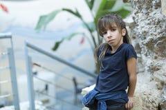 10 éénjarigenmeisje die op een rots rusten die de camera bekijken Stock Foto's