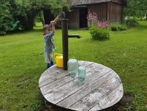 4 éénjarigenpeuter die in landbouwbedrijf met waterput werken Stock Afbeeldingen
