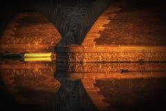 阳光在Evesham照明设备的工作员桥梁下在雅芳河的一条小船 免版税库存图片