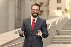 阻止信用卡和付网上付款的商人在他的手机有大厦背景 愉快的生意人 库存图片