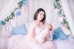 闺房礼服的年轻母亲有她的胳膊的一个婴孩的由机盖床 图库摄影