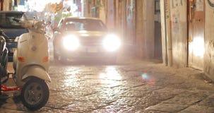 那不勒斯,意大利- 2018年10月18日:在停放的大黄蜂类滑行车附近的汽车驱动在夜狭窄的街道 大黄蜂类是意大利品牌 股票录像