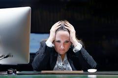 重音的妇女在计算机前面 免版税库存照片