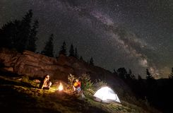 野营在山的夜夏天在夜满天星斗的天空下 免版税库存照片