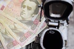 金属桶和乌克兰金钱,汽油,柴油,气体的费用的概念 重新装满汽车 钞票100 hryvnia 图库摄影