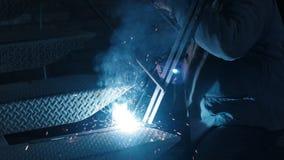 金属焊接的特写镜头 运转在铁台阶的防毒面具的公焊工 行业概念建筑 火花 影视素材