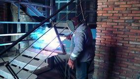 金属焊接 运转在铁台阶的防毒面具的公焊工 行业概念建筑 火花从 股票录像