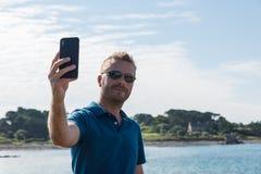 采取与智能手机的人一selfie在湖边 库存照片