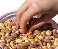 采取一些混杂的快餐米薄脆饼干、坚果和干果子的手 图库摄影