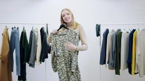 采取从某人的一件礼服手和摆在用它的成人俏丽的妇女在一间化装室 股票录像