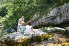 采取孩子的快照在家庭旅行的母亲由山小河 免版税库存照片