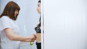采取年轻女人的测量的医生在诊所 影视素材