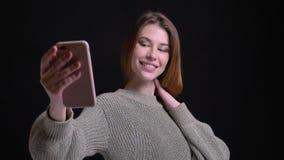 采取在电话的年轻美丽的白种人女孩特写镜头画象selfies摆在照相机前面 影视素材