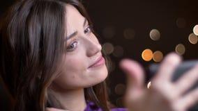 采取在电话的selfies和做空气亲吻的年轻美丽的白种人女性特写镜头画象  股票视频