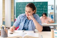 采取数学考试的年轻学生在教室 免版税库存图片