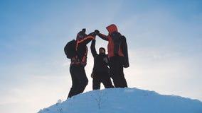 配合 小组队旅游徒步旅行者成功胜利冬天到达了山剪影阳光的上面 游人 股票录像