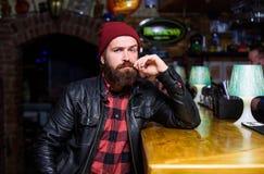 酒吧放松地方有饮料和放松 有胡子的人花费在黑暗的酒吧的休闲 残酷孤独的行家 残酷地 库存照片