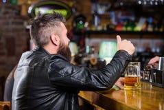 酒吧放松地方有饮料和放松 有胡子的人花费在黑暗的酒吧的休闲 放松在酒吧的行家与 库存图片