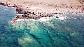 透明的波浪鸟瞰图在岩石海岸的与清楚的蓝色水的海岸线 股票录像