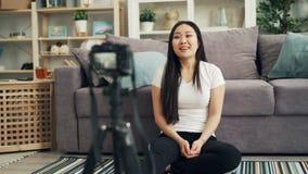 逗人喜爱的亚裔女孩女性博客作者记录谈她的互联网的vlog的录影看照相机和微笑和 股票视频