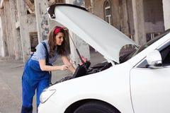 逗人喜爱的可爱的女孩审查的发动机在汽车修理店 图库摄影