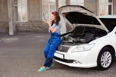 逗人喜爱的可爱的女孩审查的发动机在汽车修理店 库存照片