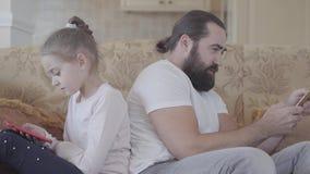 逗人喜爱的坐在客厅的沙发有smarphones的和变冷在舒适天的女儿和她的父亲 父亲和 股票录像
