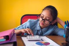 逗人喜爱的女孩戴着眼镜不耐烦与在黄色背景隔绝的书桌上的辛苦 免版税库存图片