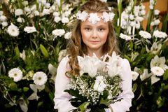 逗人喜爱的女孩画象白色礼服和花圈的在第一个圣餐背景教会门 免版税库存图片