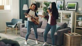 逗人喜爱的少女亚洲人和非裔美国人在遥控唱歌并且弹在家放松的吉他 影视素材