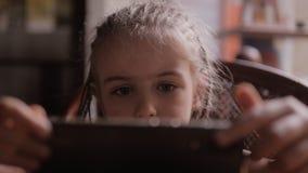 逗人喜爱的儿童女孩面孔画象手表动画片通过智能手机 影视素材