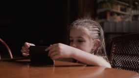 逗人喜爱的儿童女孩面孔画象手表动画片通过智能手机 股票录像