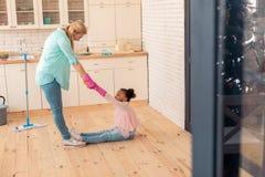 逗人喜爱的滑稽的女孩坐清洗厨房的地板一会儿母亲 库存图片